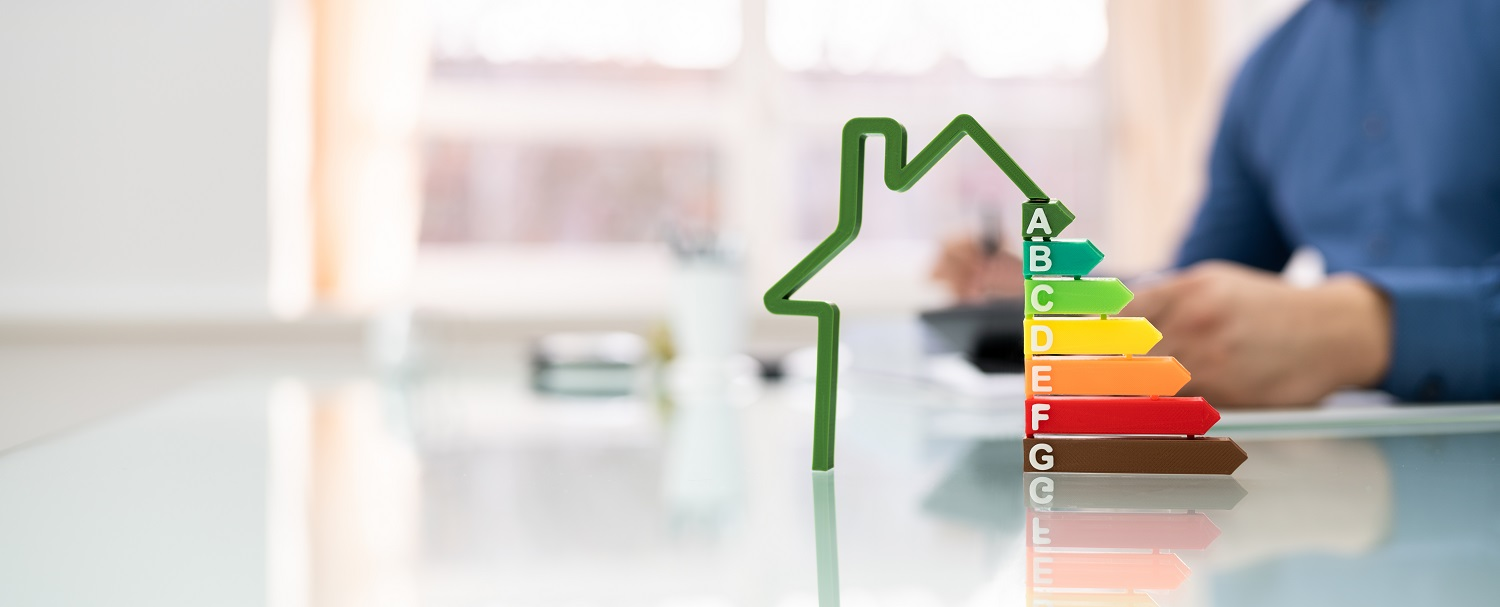 Image of a house with energy raing A-G with man on calculator in background